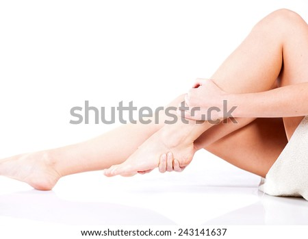 Young woman massaging her painful ankle - stock photo