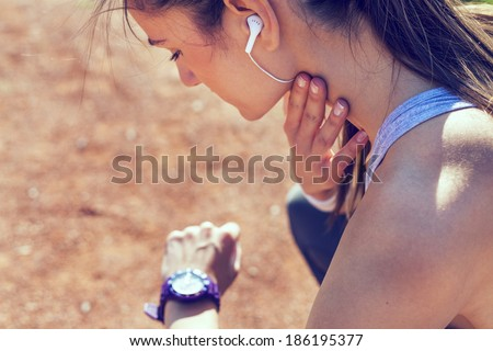 Young woman measuring heart rate after running - stock photo