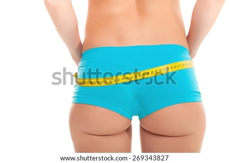 Young Woman measuring her waist - Stock Image - stock photo