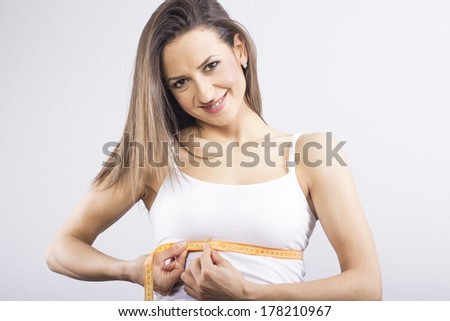 Young woman measuring her waist with tape. - stock photo