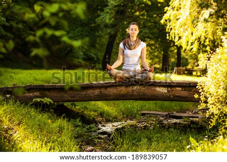 Young woman meditate in park. - stock photo