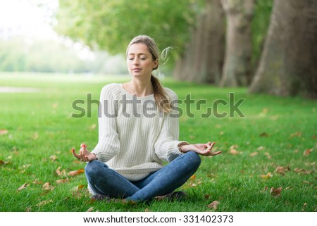 Young woman meditating and Yoga in a park  - stock photo