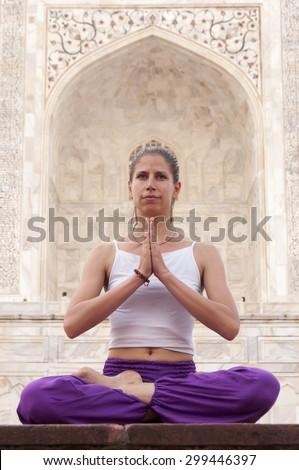 Young woman  meditating at Taj Mahal, India - stock photo