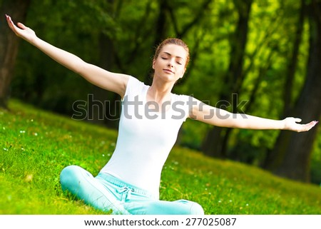 Young woman meditating in park - stock photo
