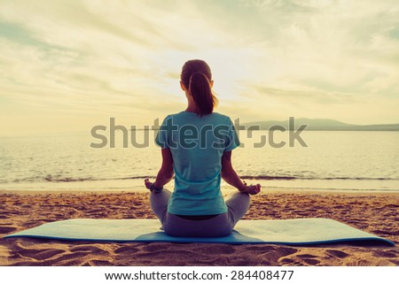 Young woman meditating in pose of lotus on beach near the sea at sunset in summer, rear view - stock photo