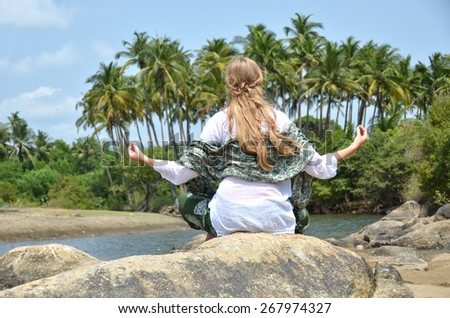 Young woman meditating on Agonda beach. Goa, India - stock photo