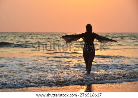 Young woman meditating on Agonda beach. South Goa, India - stock photo