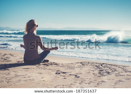 Young woman meditating on the beach  - stock photo