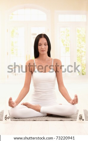 Young woman meditating with closed eyes in bright living room.? - stock photo