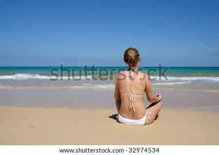 Young woman meditation on the beach. Fuerteventura, Canary Islands, Spain - stock photo