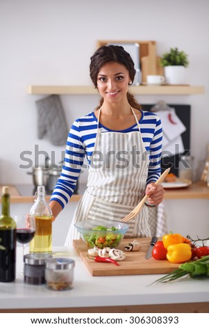 Young woman mixing fresh salad, standing near desk - stock photo