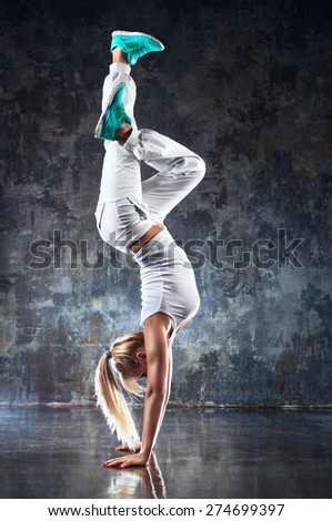 Young woman modern dancer standing on hands. On stone wall background. - stock photo