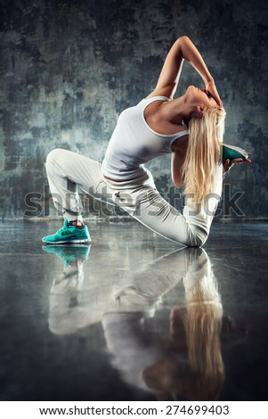 Young woman modern dancer stretching legs. On dark stone wall background. - stock photo