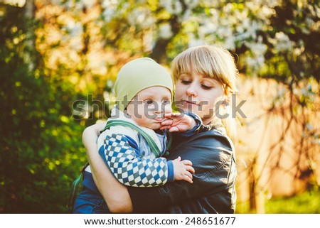 Young Woman Mother Hugging Her Baby Son. Outdoor Spring Portrait - stock photo