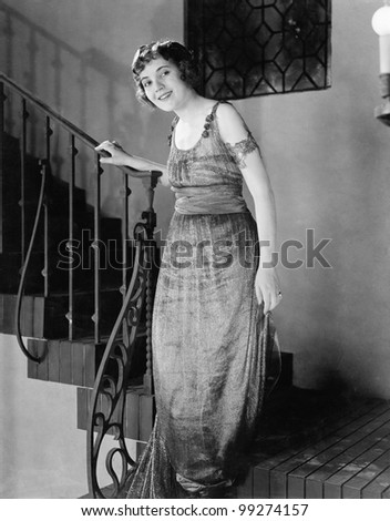 Young woman moving down a staircase and smiling - stock photo