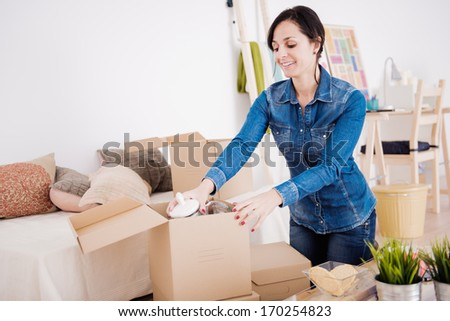 Young woman moving into a new apartment. - stock photo