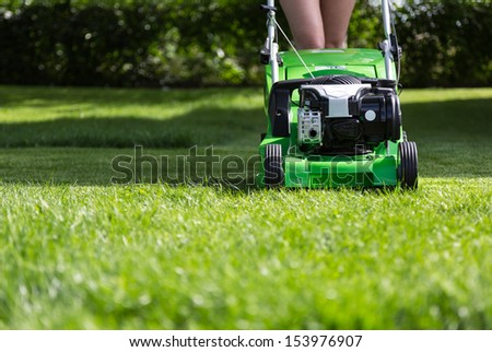 Young woman mowing the lawn. - stock photo