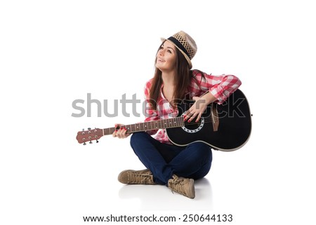 Young woman musician with guitar wearing shirt and hat sitting on a floor and smiling. White background. - stock photo