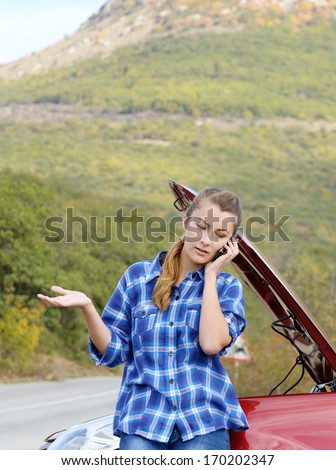 Young woman near broken car speaking by phone needs assistance - stock photo