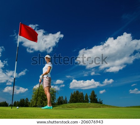 Young woman near hole with red flag on a golf club field  - stock photo