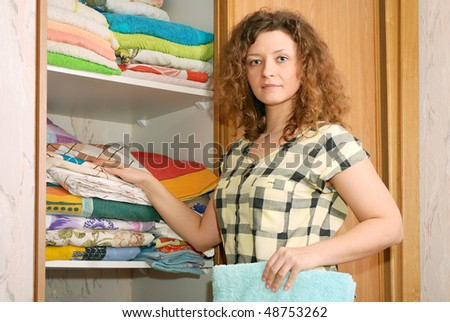 young woman near sliding-door wardrobe with bed linen - stock photo