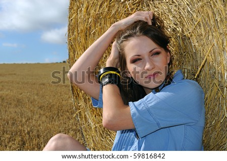Young woman near the straw bales - stock photo