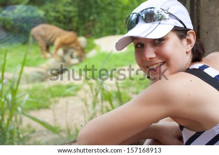 young woman near tiger in zoo - stock photo