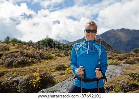 Young woman nordic walking in Himalaya Mountains in Nepal - stock photo