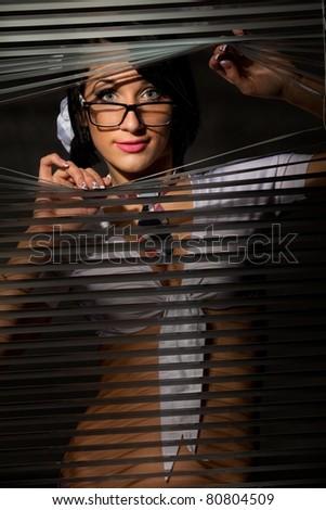 Young Woman observes through a jalousie - stock photo