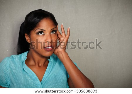 Young woman of african ethnicity looking sick while standing against grey texture background - stock photo