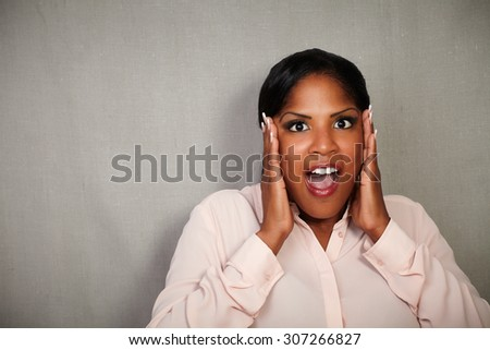 Young woman of afro-american ethnicity looking surprised at the camera - copy space - stock photo