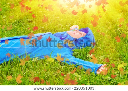 Young woman on a autumn day lying in grass - stock photo