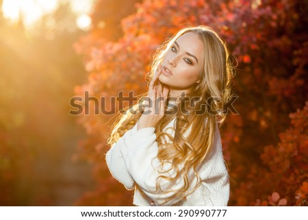 young woman on a background of red and yellow autumn leaves with beautiful curly hair - stock photo