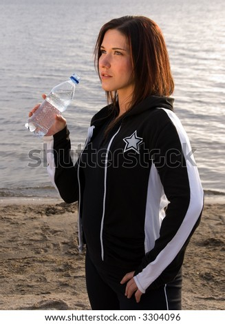 young woman on a beach in a track suit holds bottled water - stock photo