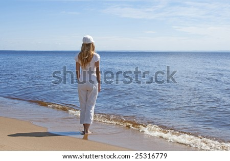 Young woman on a beach, looking at water. - stock photo