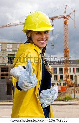 Young woman on a building site in workwear with thumb up - stock photo
