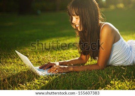 young woman on a grass in the park or garden using laptop - stock photo