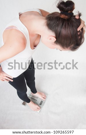 young woman on a weighing scale - stock photo