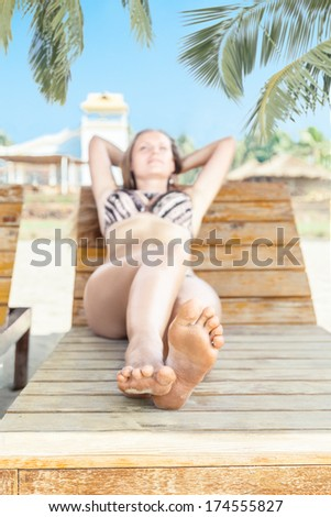 Young woman on beach chair and relaxing in tropical resort - stock photo