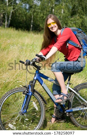young woman on bicycle  rides from green  park - stock photo