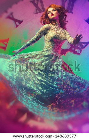 Young woman on clock background. Surreal colors. - stock photo