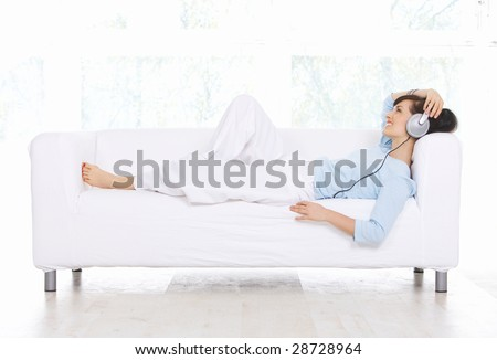 Young woman on couch and listen to the music - stock photo