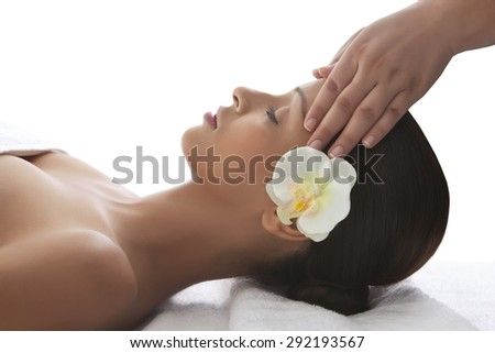 Young woman on massage table getting head massage - stock photo