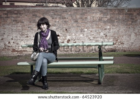 Young woman on park bench. Edgy processing. - stock photo