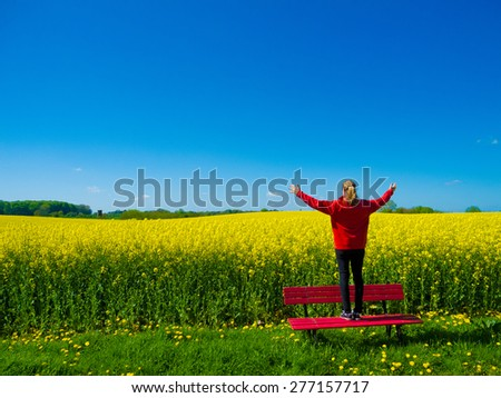 young woman on red bench in front of blooming canola field - stock photo
