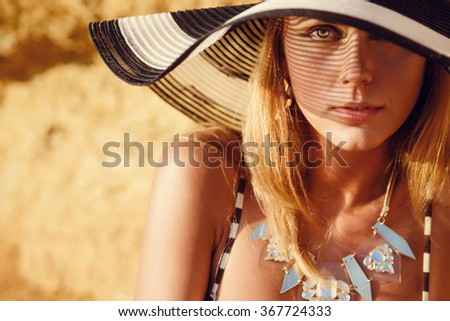 young woman on sand beach. Summer trendy fashion woman posing on the rocks alone on the ocean seashore. Outdoors lifestyle portrait - stock photo