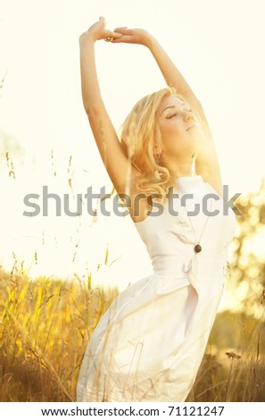 Young woman on summer field portrait. Bright sunlight effect. - stock photo
