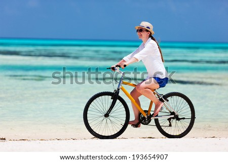 Young woman on summer vacation biking at tropical beach - stock photo
