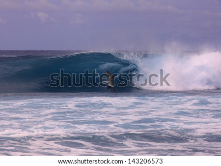 young woman on surfboard riding a big wave in hawaii - stock photo