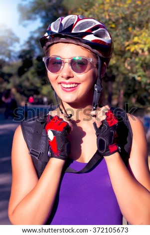 Young woman on the bicycle wearing on the helmet.Bike helmet - woman putting biking helmet on outside during bicycle ride.Woman wearing biking helmet. Close-up portrait of female cyclist.Cheerful lady - stock photo